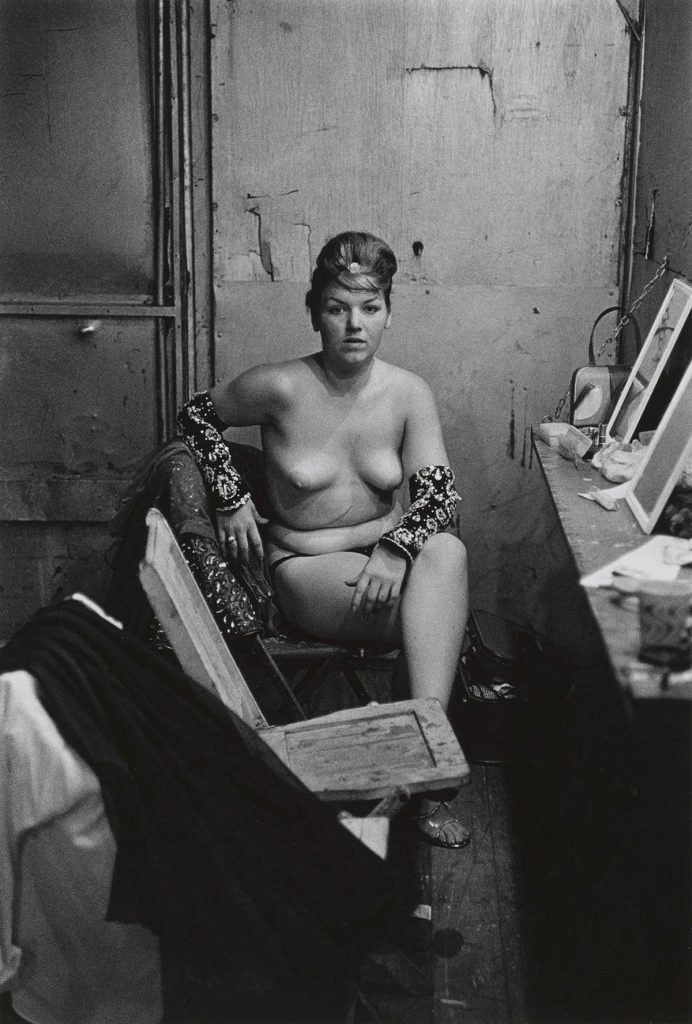 Diane Arbus. Stripper with bare breasts sitting in her dressing room, Atlantic City, N.J. 1961.